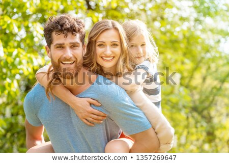 Stock fotó: Strong Man Supporting His Family By Carrying Wife And Son Piggyback