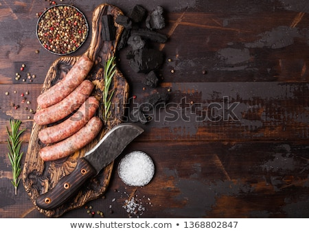 Raw beef and pork sausage on old chopping board with vintage knife and fork on dark wooden backgroun stock photo © DenisMArt