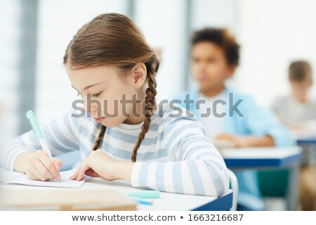 Közelkép boldog iskolás lány néz kamera osztályterem Stock fotó © wavebreak_media