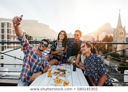 happy friends taking selfie at rooftop party stock photo © dolgachov