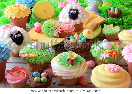 cupcakes with easter eggs and candies on plate stock photo © dolgachov