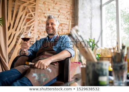Happy professional artist with glass of wine toasting for success Stock photo © pressmaster