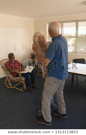 side view of active senior couple dancing with a senior man reading on a chair at nursing home stock photo © wavebreak_media
