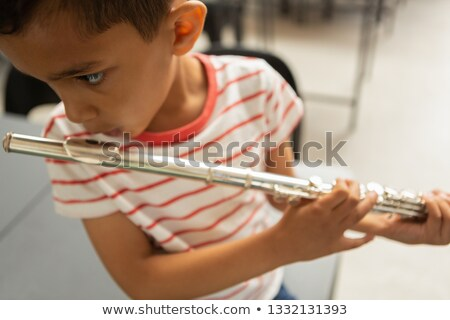 Close-up of focused mixed-race schoolboy playing flute in a classroom at elementary school Stock photo © wavebreak_media