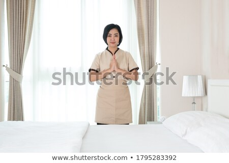 Pretty young hotel room service staff in uniform standing in front of camera Stock photo © pressmaster