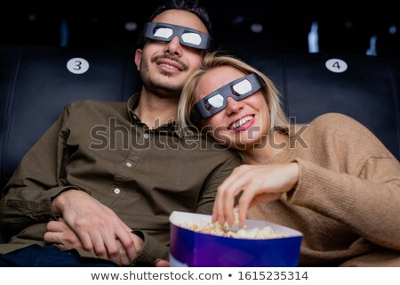 Happy young amorous couple in 3d eyeglasses watching interesting action movie Stock photo © pressmaster