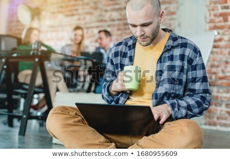 Hip worker in a startup coding with laptop sitting on skateboard Stock photo © Kzenon
