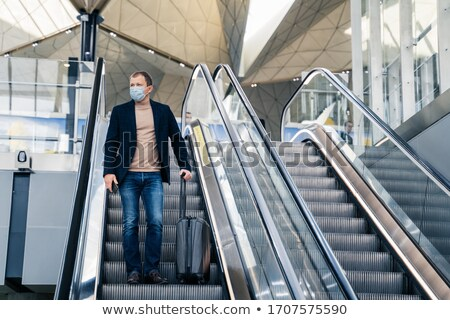 Man wears medical face mask, poses on escalator in airport, arrives from abroad, holds mobile phone  Stock photo © vkstudio