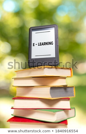 Electronic book reader laying on the book outdoors Stock photo © AndreyKr