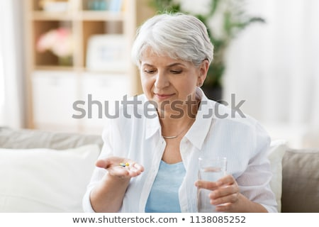elderly woman taking a pill stock photo © photography33