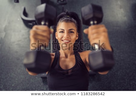 woman lifting dumbbell in gym stock photo © ambro