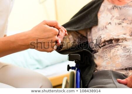 caregiver holding senior ladys hand stock photo © melpomene
