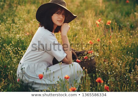 woman in red dress holding yellow flowers basket and sits stock photo © feedough