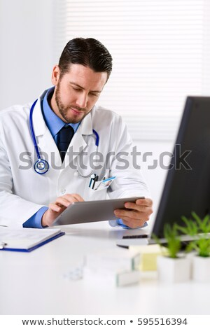 Thoughtful male doctor holding tablet compute Stock photo © deandrobot