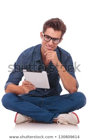 Jóképű férfi ül lábak keresztbe megérint áll fiatal Stock fotó © feedough