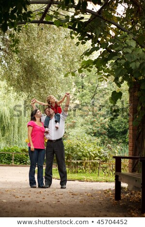 Parents and little girl in summer garden in plant tunnel. Girl sits at father on shoulders. Stock photo © Paha_L
