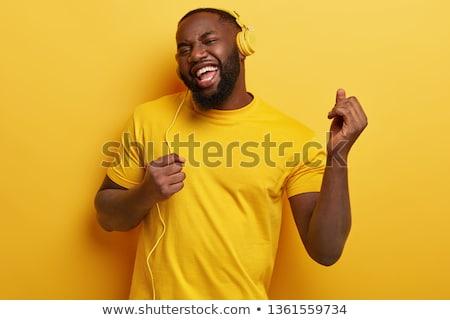 Fiatal szakállas férfi hallgat zene fülhallgató Stock fotó © deandrobot