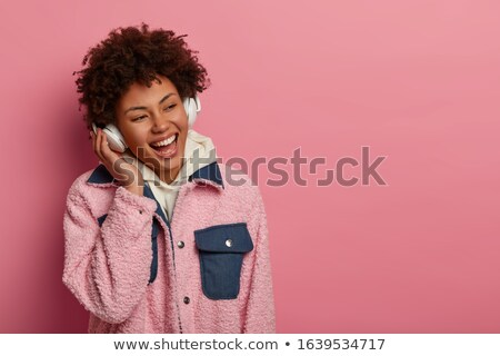 happy young lady listening music looking aside stock photo © deandrobot