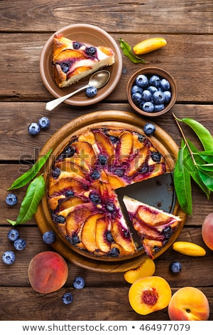 Peach cheese cake or pie with fresh blueberry on wooden rustic background, top view, closeup Stock photo © yelenayemchuk