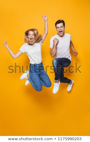 happy young loving couple jumping isolated stock photo © deandrobot