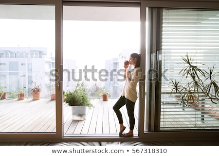 woman relaxing by door with cup stock photo © is2