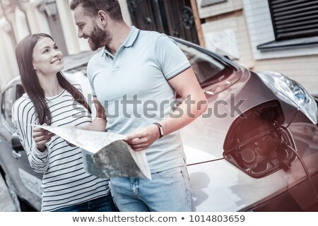 Stock photo: Young women with map by electric car