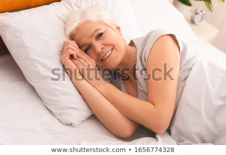 Woman lying in bed smiling stock photo © monkey_business