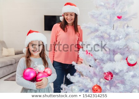 girl standing behind a fir-tree, smiling Stock photo © IS2