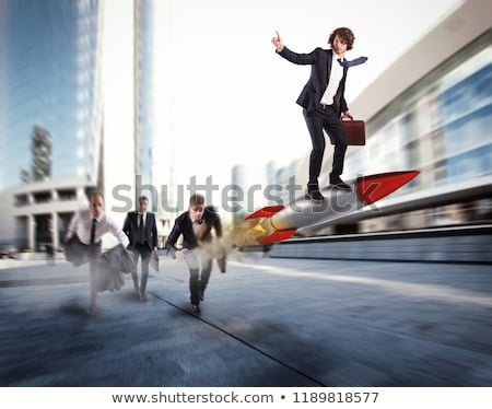 Push to reach the goals before the others. Businessman wins a challenge riding a rocket Stock photo © alphaspirit