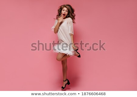 Full length portrait of a shocked young girl in dress jumping Stock photo © deandrobot