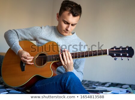 teenage boy playing acoustic guitar in bed stock photo © boggy