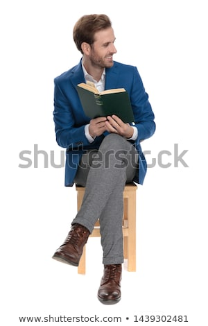 happy elegant man sitting and showing his book to side stock photo © feedough