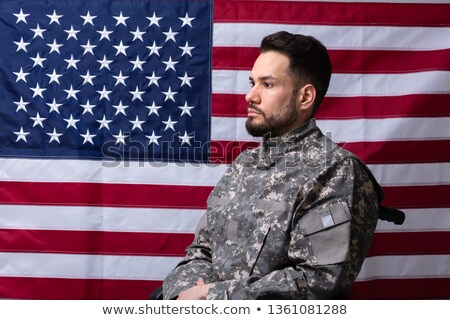 veteran sitting in wheelchair in front of an american flag stock photo © andreypopov