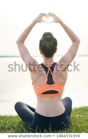 Rear view of slim girl in sportswear sitting with crossed legs on shore Stock photo © pressmaster