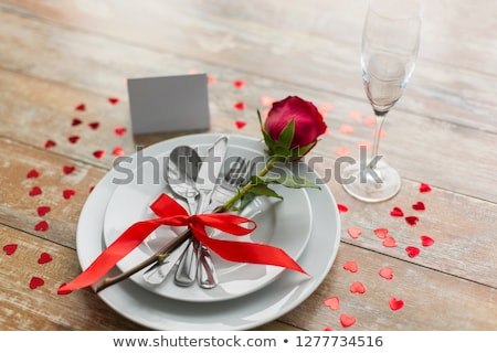 close up of cutlery tied with red ribbon on plates Stock photo © dolgachov