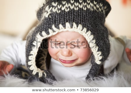 Crying baby boy with woolen cap. stock photo © lichtmeister