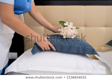 Chamber maid bending over bed while putting fresh flowers on top of pillow Stock photo © pressmaster