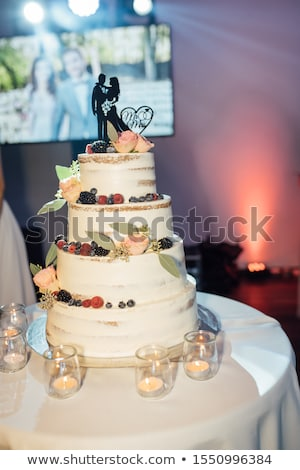 pink and white wedding cake with roses with candles around stock photo © ruslanshramko