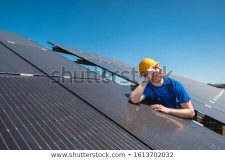 Manutenção trabalhador em pé painéis solares olhando sol Foto stock © Kzenon