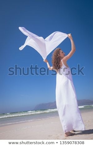 Low angle view of happy young Caucasian woman holding scarf at beach on sunny day. She seems relaxed Stock photo © wavebreak_media