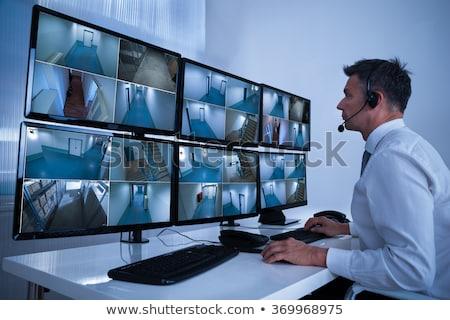 Man In Control Room Monitoring CCTV Footage Stock photo © AndreyPopov