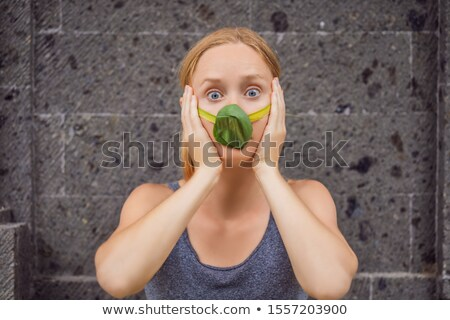 Woman made himself a face mask from the leaves to protect himself from air pollution. Air purificati Stock photo © galitskaya