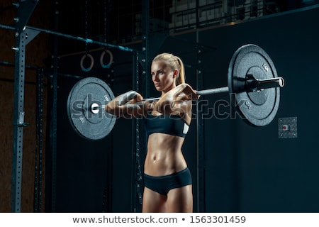 Blond woman in sportswear holding weights Stock photo © photography33