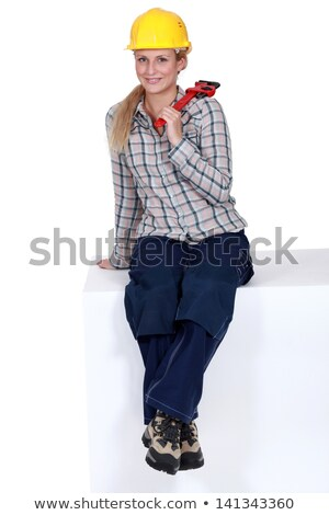 Tradeswoman sitting on a block and holding a pipe wrench Stock photo © photography33