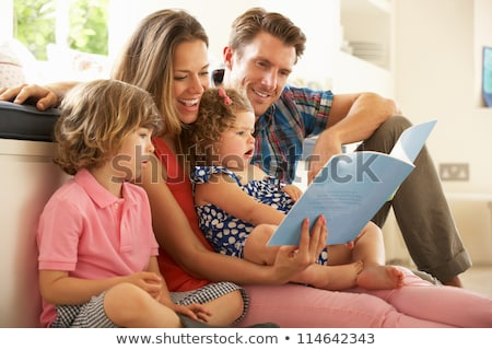 Parents Sitting With Child Reading Story Indoors Stock photo © HASLOO