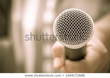 Stock photo: hand holding microphone in sound record room