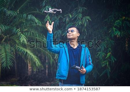 jóképű · férfi · napszemüveg · kéz · arc · néz · kamera - stock fotó © stryjek