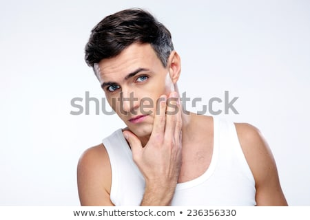 Young man after shaving over gray background Stock photo © deandrobot