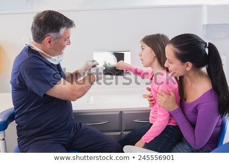 pediatric dentist examining young patient with her mother stock photo © wavebreak_media