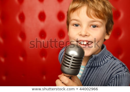 Singing boy with microphone on rack against red wall. Close up. Horizontal format. Stock photo © Paha_L